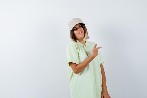 T- 셔츠에 젊은 여성, 모자 멀리 가리키고 행복, 전면보기를 찾고.