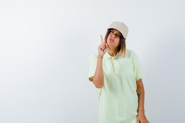 T- 셔츠에 젊은 여성, 모자를 가리키고 주저, 전면보기를 찾고.