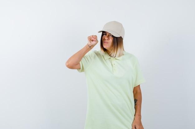 T- 셔츠에 젊은 여성, 얼굴 근처 주먹을 제기 하 고 심각한, 전면보기를 찾고 모자.