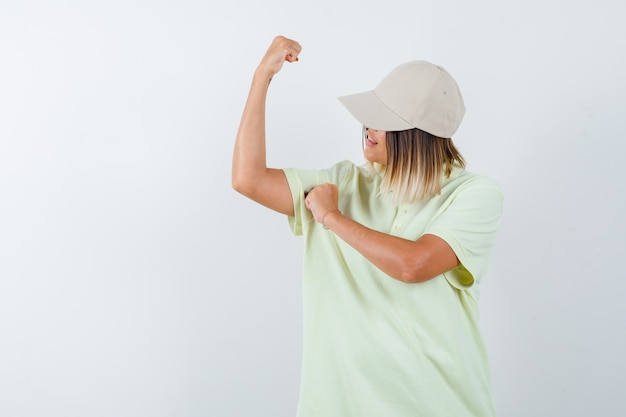 Tシャツを着た若い女性、腕の筋肉を示し、誇らしげに見えるキャップ、正面図。