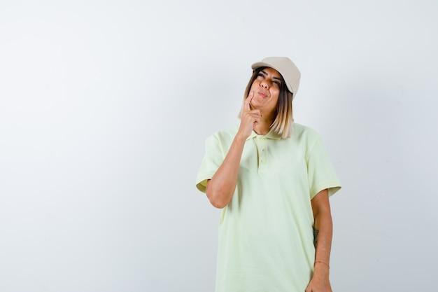 T- 셔츠에 젊은 여성, 생각 포즈에 서있는 모자와 사려 깊은, 전면보기를 찾고.