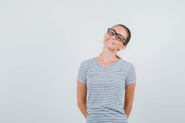 Tシャツを着た若い女性、背中に手を置いてキュートに見えるメガネ、正面図。