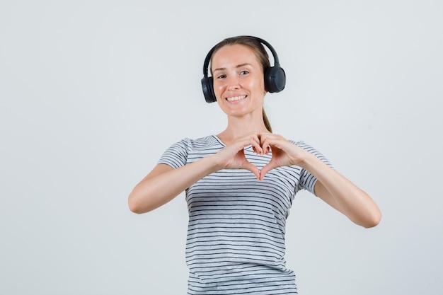 Tシャツを着た若い女性、ハートのジェスチャーを示し、陽気に見えるヘッドフォン、正面図。