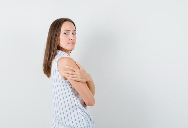 Молодая женщина в футболке держит руку на другой руке и выглядит уверенно.