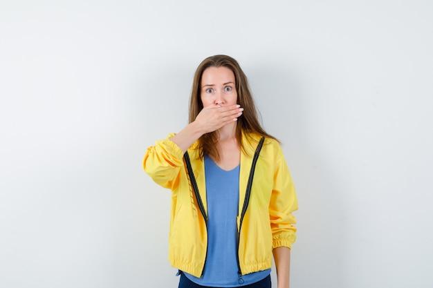 Tシャツを着た若い女性、口に手を保持し、ショックを受けた、正面図を見てジャケット。