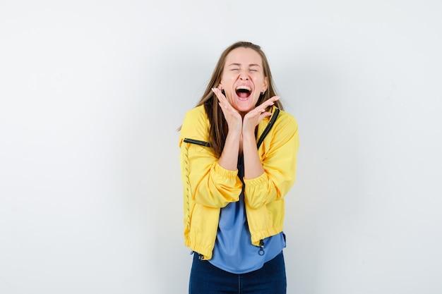 Tシャツ、あごの下で手をつないで、幸せそうに見えるジャケット、正面図の若い女性。