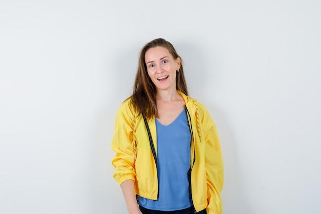 Молодая женщина в футболке, куртке смотрит в камеру и выглядит очаровательно, вид спереди.
