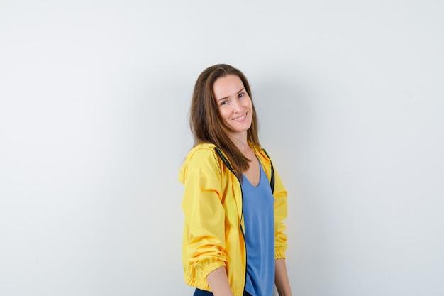 Молодая женщина в футболке, куртке смотрит в камеру и выглядит восхитительно, вид спереди.