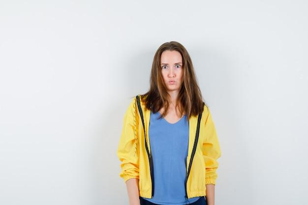 Молодая женщина в футболке, куртке, глядя в камеру и озадаченно глядя, вид спереди.