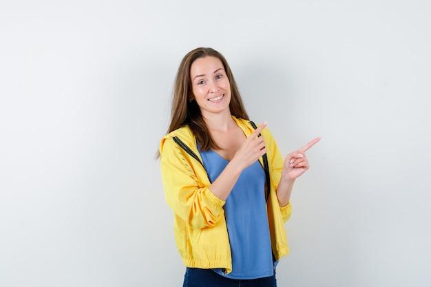 Tシャツを着た若い女性、右上隅を指して自信を持って正面から見たジャケット。