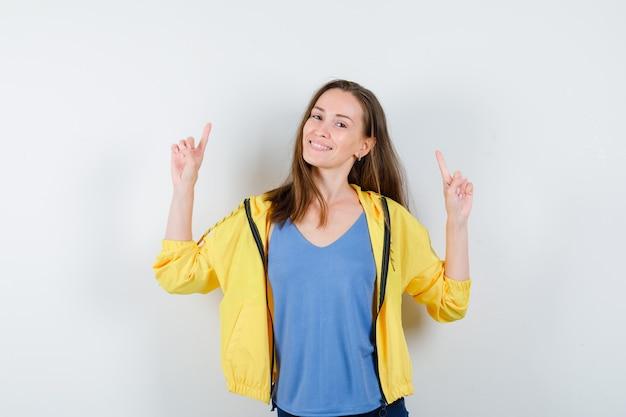 Tシャツを着た若い女性、上向きで自信を持って見えるジャケット、正面図。