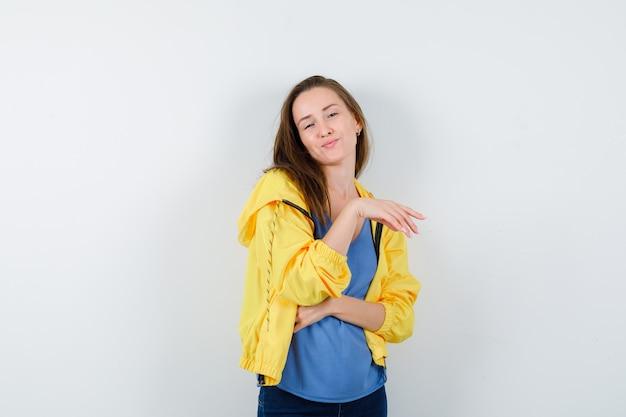 Tシャツを着た若い女性、立ったままポーズをとるジャケット、楽しい正面図。