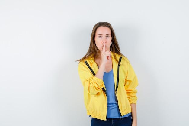 Tシャツを着た若い女性、沈黙のジェスチャーを示し、賢明に見えるジャケット、正面図。