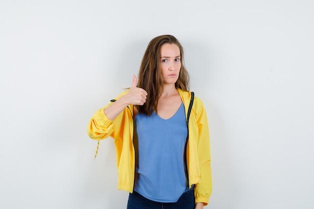 Tシャツを着た若い女性、親指を上に向けて自信を持って見えるジャケット、正面図。