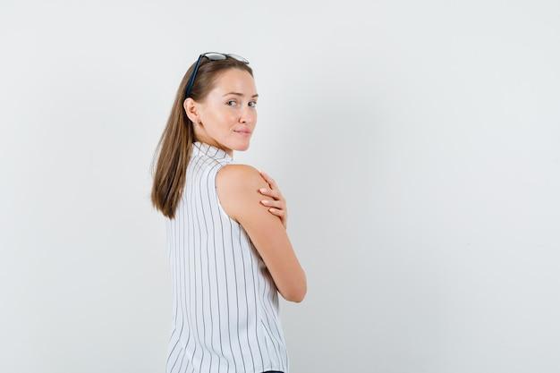 Молодая женщина в футболке, оглядываясь назад с рукой на руке и выглядя обнадеживающей.