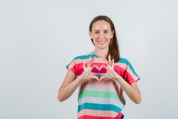 Молодая женщина в футболке делает форму сердца пальцами и выглядит веселой, вид спереди.