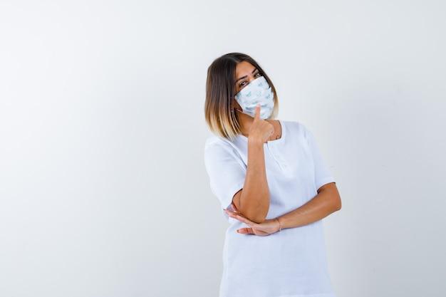 T- 셔츠에 젊은 여성, 위로 향하고 명랑 한, 전면보기를 찾고 마스크.