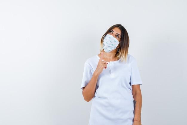 T- 셔츠, 마스크 가리키는 사려 깊은, 전면보기에 젊은 여성.