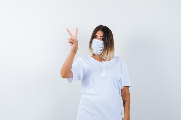 Tシャツ、勝利のサインを示し、幸運に見えるマスク、正面図の若い女性。