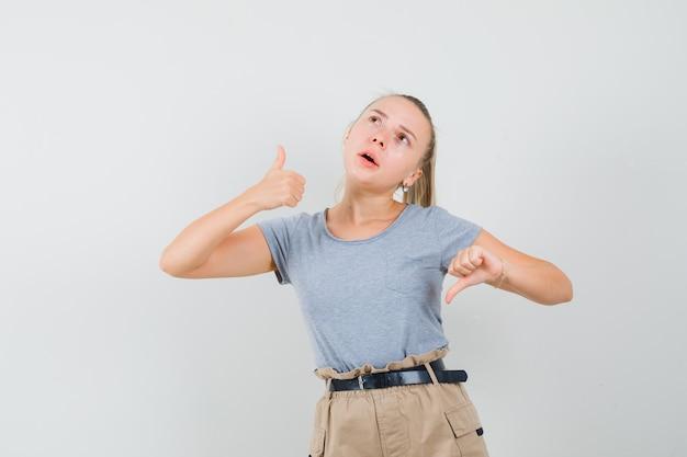 Tシャツを着た若い女性、親指を上下に見せて優柔不断に見えるズボン、正面図。
