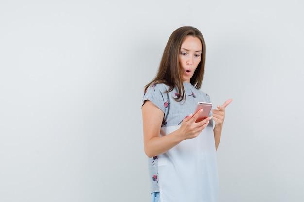 携帯電話を指して驚いて見えるtシャツの若い女性、正面図。