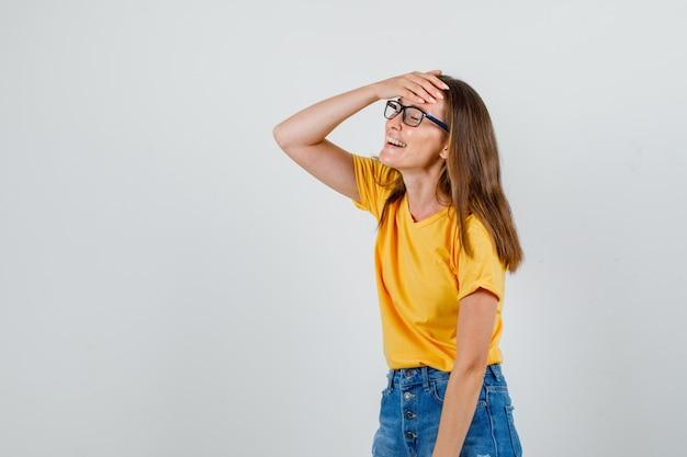 Tシャツ、ショートパンツ、額に手で笑っているメガネの若い女性。