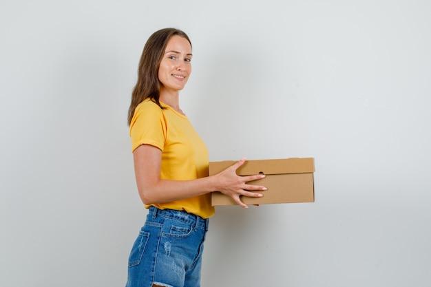 Tシャツ、段ボール箱を保持し、笑顔のショートパンツの若い女性。