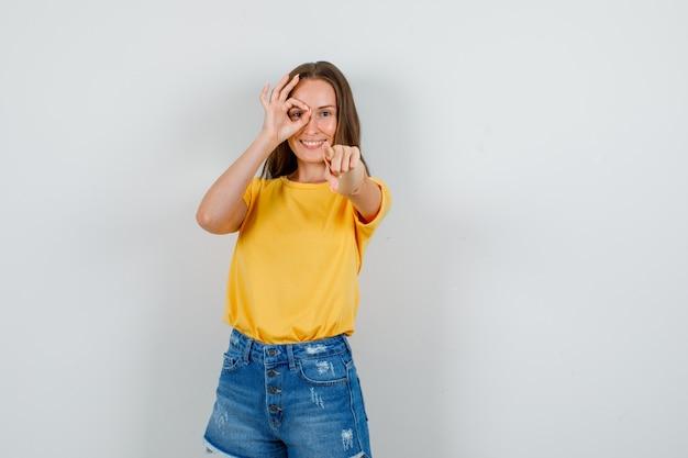 Молодая женщина в футболке, шортах указывает на камеру со знаком ок на глазах и выглядит веселой