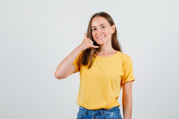 Tシャツを着た若い女性、電話のジェスチャーを示し、幸せそうに見えるショートパンツ