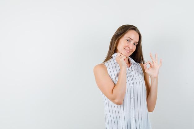 襟を保持し、陽気に見えながら、okサインを示すtシャツの若い女性、正面図。