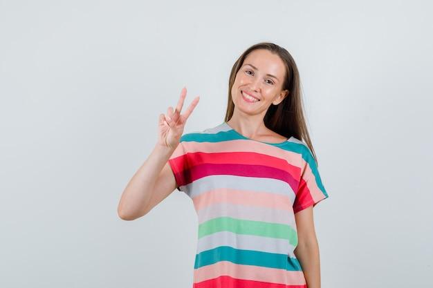 勝利のサインを示し、陽気に見えるtシャツの若い女性、正面図。