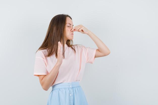 Tシャツを着た若い女性、悪臭を感じ、嫌な顔をしているスカート、正面図。