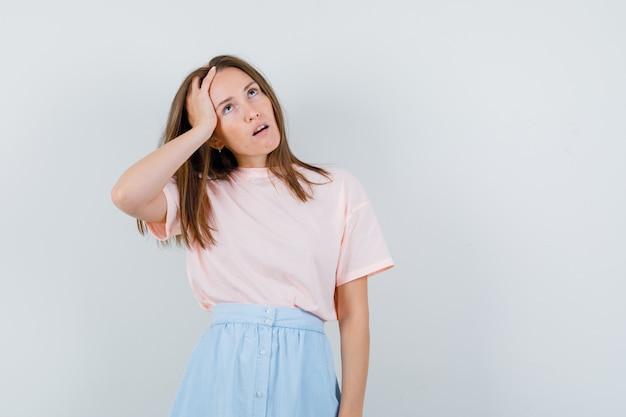 Молодая женщина в футболке, юбка смотрит вверх и задумчиво, вид спереди.
