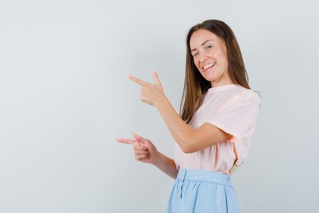 Tシャツを着た若い女性、目をまばたきしながら目をそらし、幸せそうに見えるスカート、正面図。