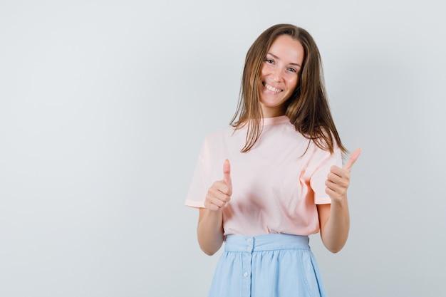 Tシャツを着た若い女性、親指を立てて幸運に見えるスカート、正面図。