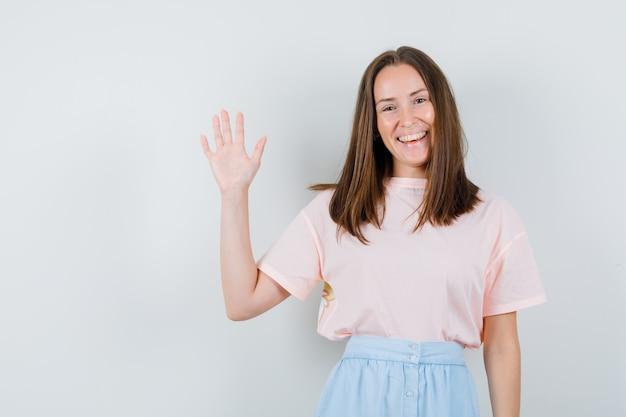 Tシャツを着た若い女性、挨拶と幸せそうに見えるために手を振るスカート、正面図。