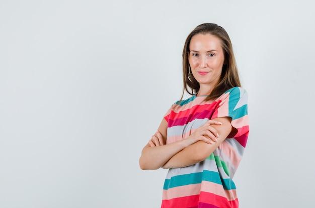 腕を組んで立っているtシャツの若い女性、正面図。