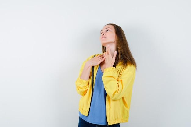 Tシャツを着た若い女性が首の肌に触れ、繊細な正面図を見せています。