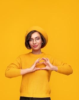 Молодая женщина в модном берете и свитере улыбается в камеру и показывает сердце возле груди, показывая любовь на желтом фоне