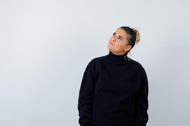 タートルネックのセーターを着た若い女性が見上げて思慮深く、正面図。