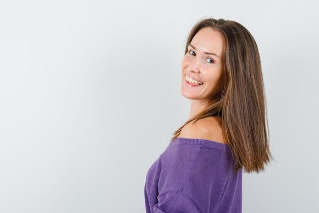 カメラを見て、陽気に見える紫のシャツの若い女性。