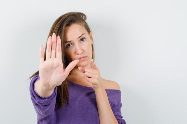 停止ジェスチャーでカメラを指して真剣に見える紫色のシャツを着た若い女性、正面図。