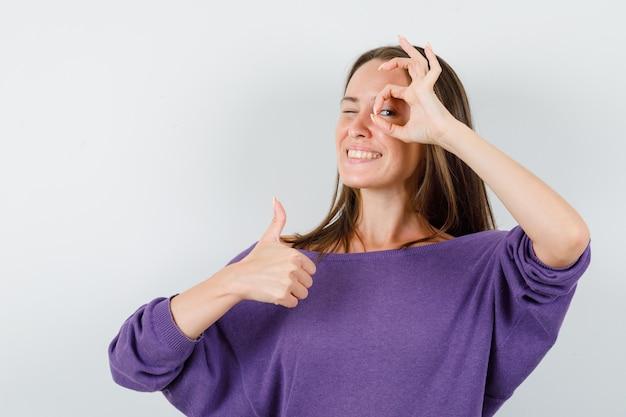 紫色のシャツを着た若い女性は、親指を上に向けて大丈夫なジェスチャーを示し、陽気に見えます。