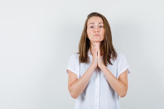 祈って無力に見える白いブラウスの若い女性