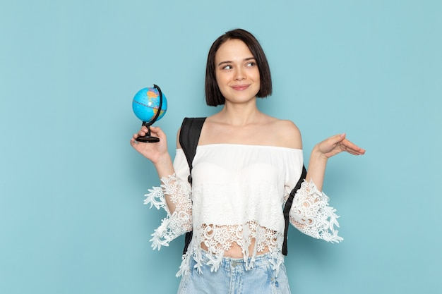 Молодая женщина в белой рубашке и черной сумке держит глобус на синем