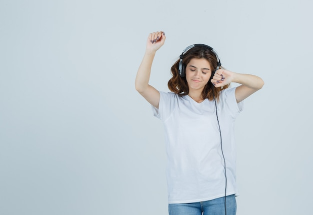 白いtシャツを着た若い女性、ヘッドフォンで音楽を楽しんで、陽気に見えるジーンズ、正面図。