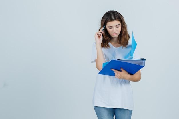 白いtシャツ、フォルダーとペンを保持し、物思いにふけるジーンズ、正面図の若い女性。