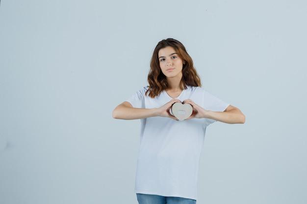 흰색 t- 셔츠, 청바지 선물 상자를 들고 자신감, 전면보기를 찾고있는 젊은 여성.
