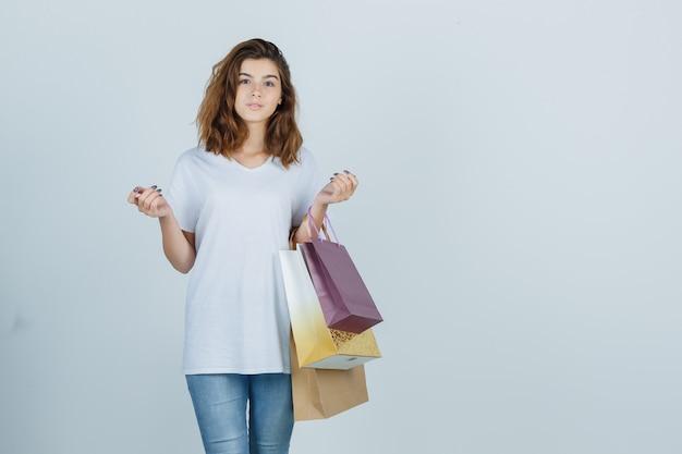 白いtシャツ、紙袋を保持し、魅力的に見えるジーンズ、正面図の若い女性。