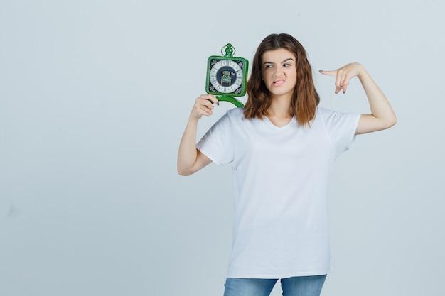 白いtシャツを着た若い女性、時計を指しているジーンズ、眉をひそめている顔と困った顔、正面図。